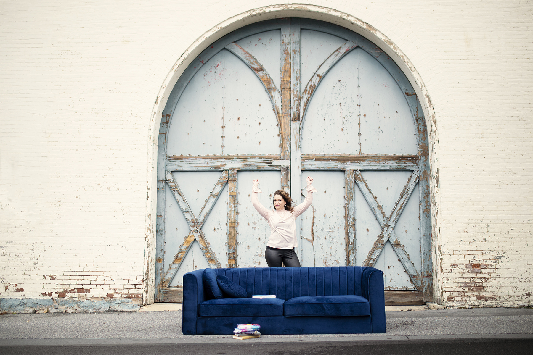 arms in the air behind blue velvet couch