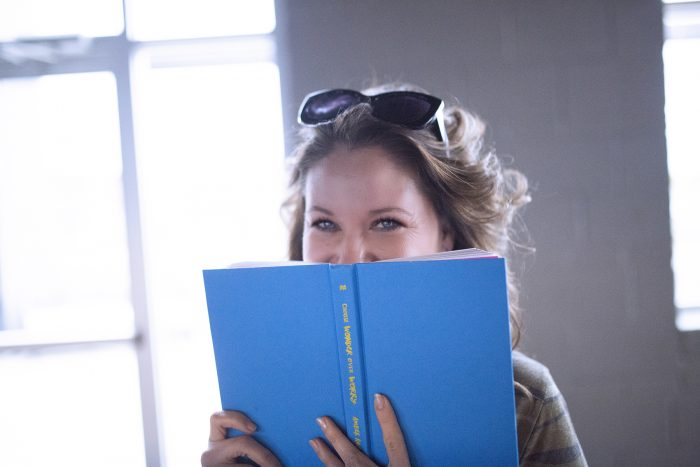 smiling behind blue book